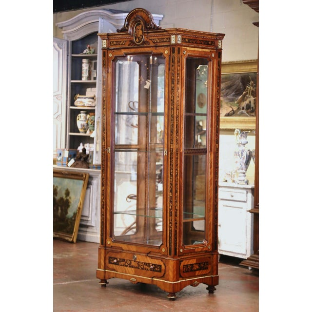 This elegant, antique fruitwood display cabinet was crafted in France, circa 1880. The tall vitrine stands on bun feet...