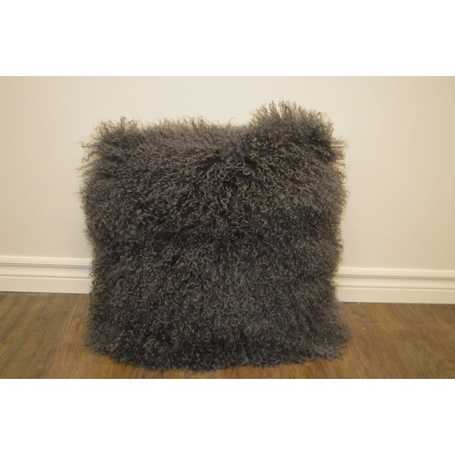 Large decorative pillows made with a curly lamb's wool skin. They are very fluffy and cozy.