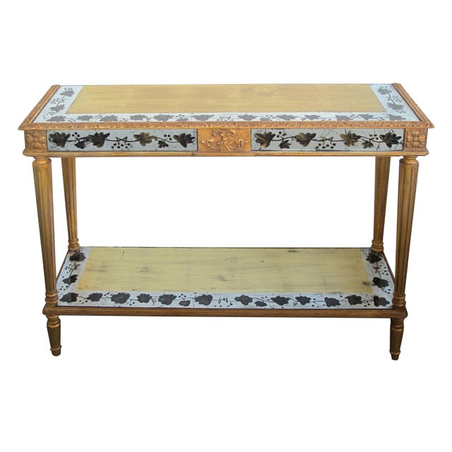 the console with silver and gold eglomise mirrored panels of meandering floral vines; all above fluted legs and lower shelf