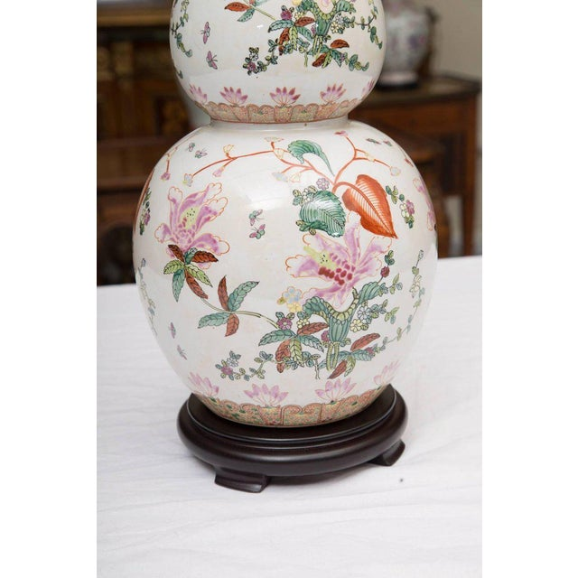 This pair of gourd shaped table lamps has a white background hand-painted with a floral design in the French manner....