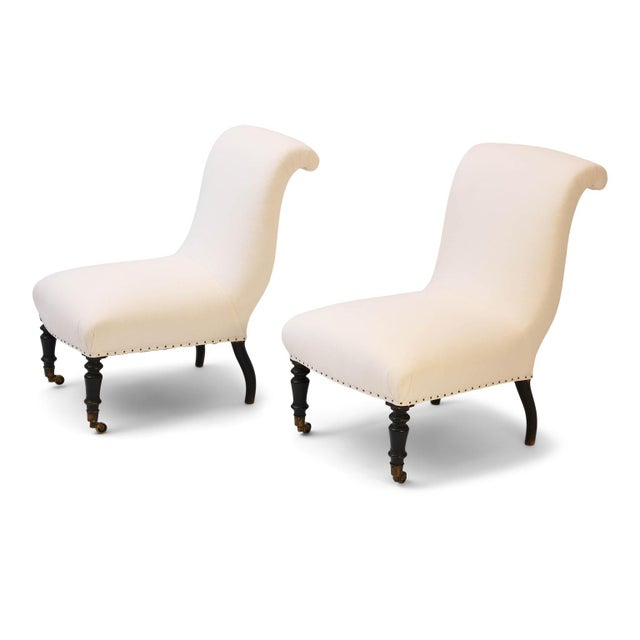 Pair of Napoleon III slipper chairs upholstered in white ticking. Roll-top back and front legs on casters. Sold as a pair...