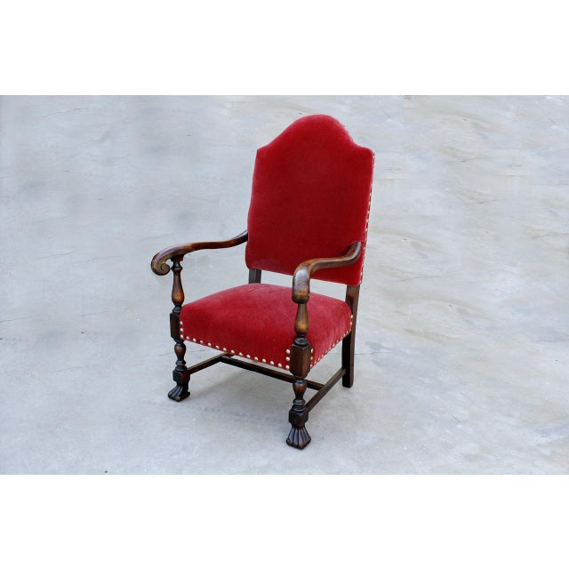 American Empire style armchair with tapered high back and ornate mahogany frame. This statement piece features...