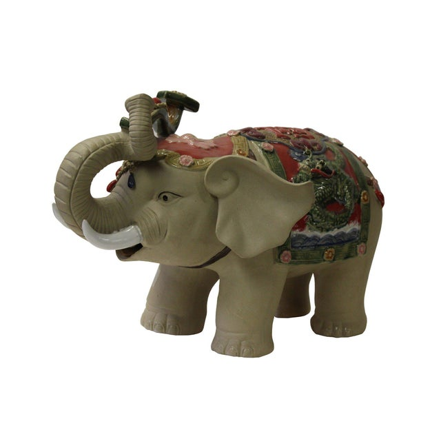 This is a delicate handmade elephant figure with plain skin color and charm accent on the body. The elephant trunk is...