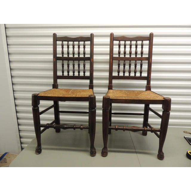 Pair of English country antique wood dining chairs with rush seats. Harlequin spindle backs. Georgian Elm and oak wood....